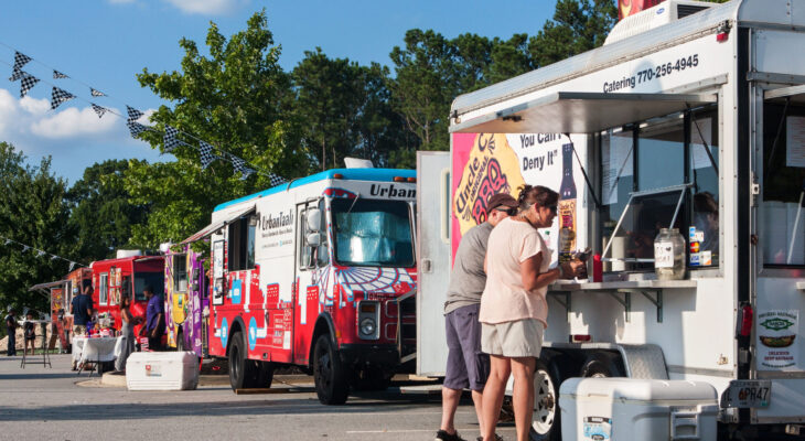 row of colorful food trucks serving customers