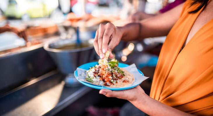 woman wearing an orange dress eating a taco on a blue plate