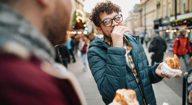 man wearing winter clothes and eating a sandwich while talking to a friend