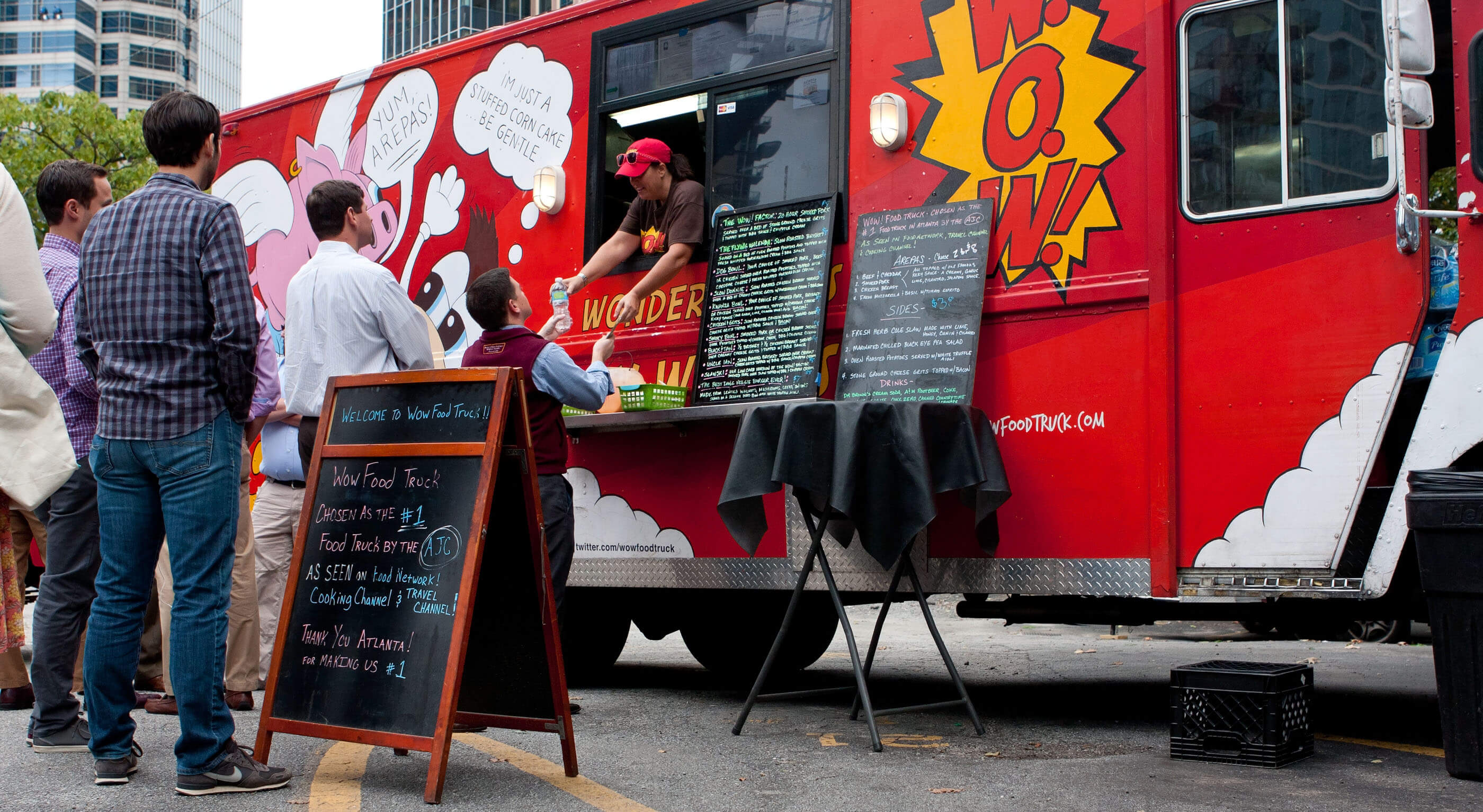 red food truck owner serving a group of customers