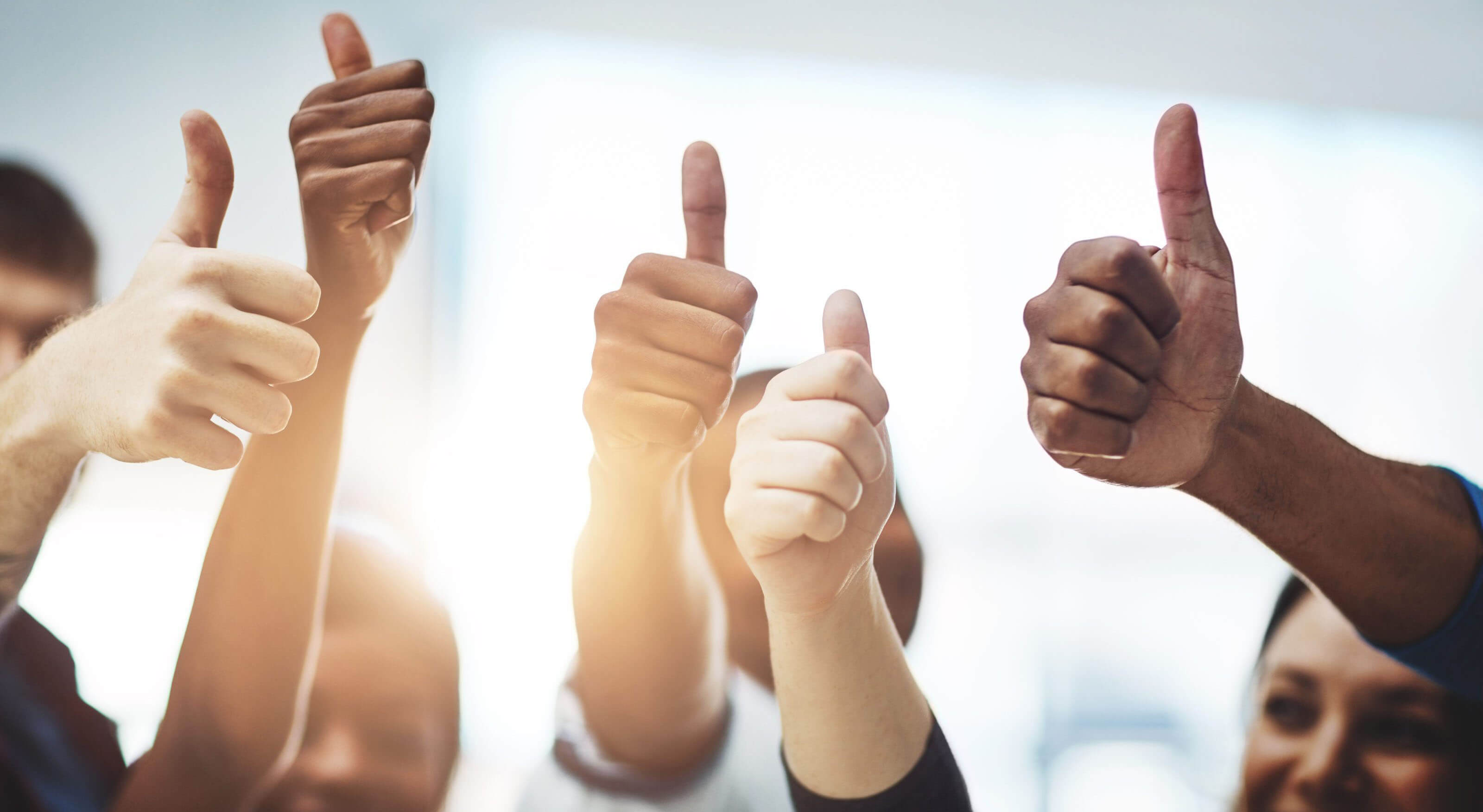 diverse group of people doing thumbs up indicating success
