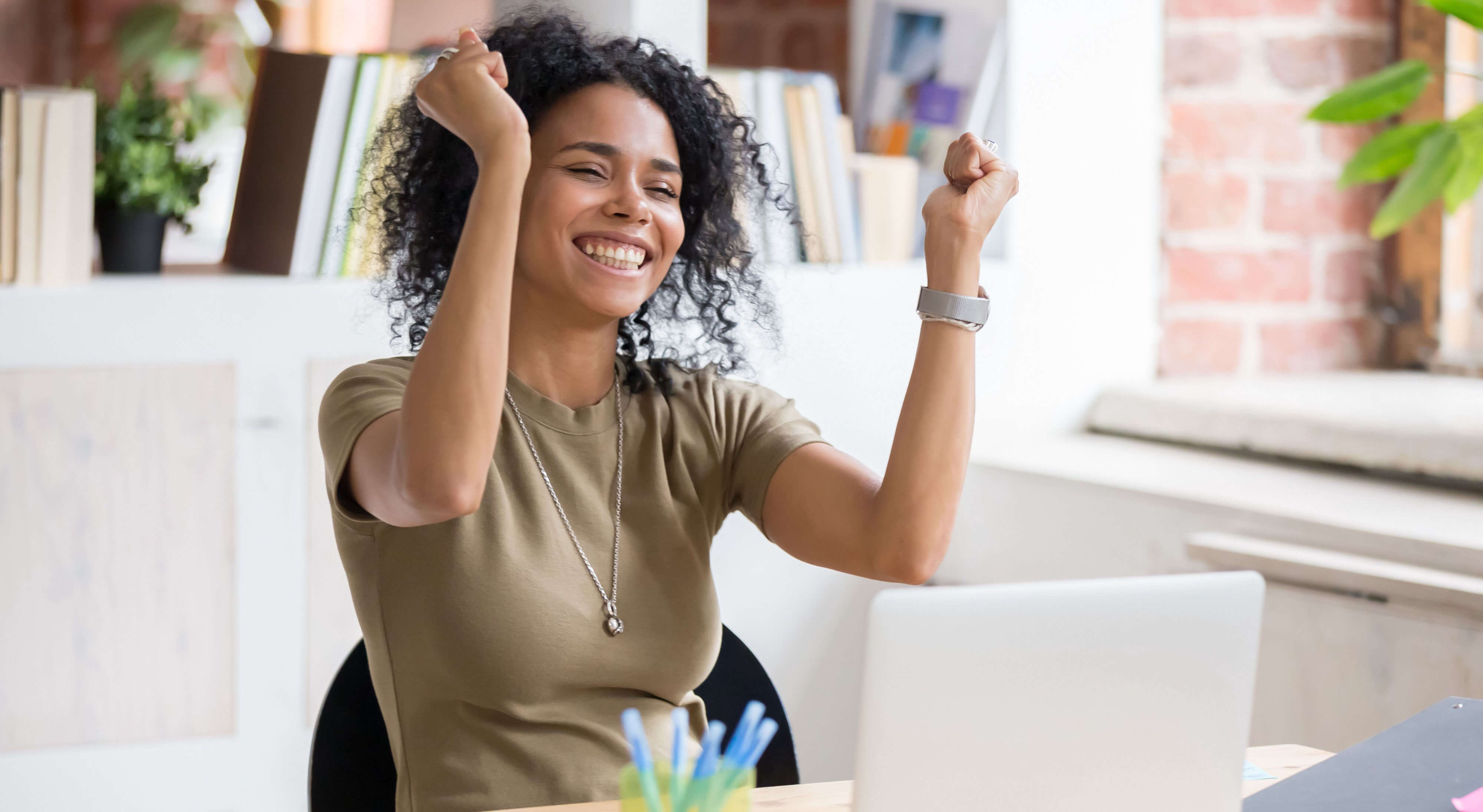 motivated woman smiling with both fists raised