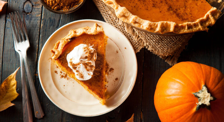 pumpkin pie on a plate on a dark wooden table