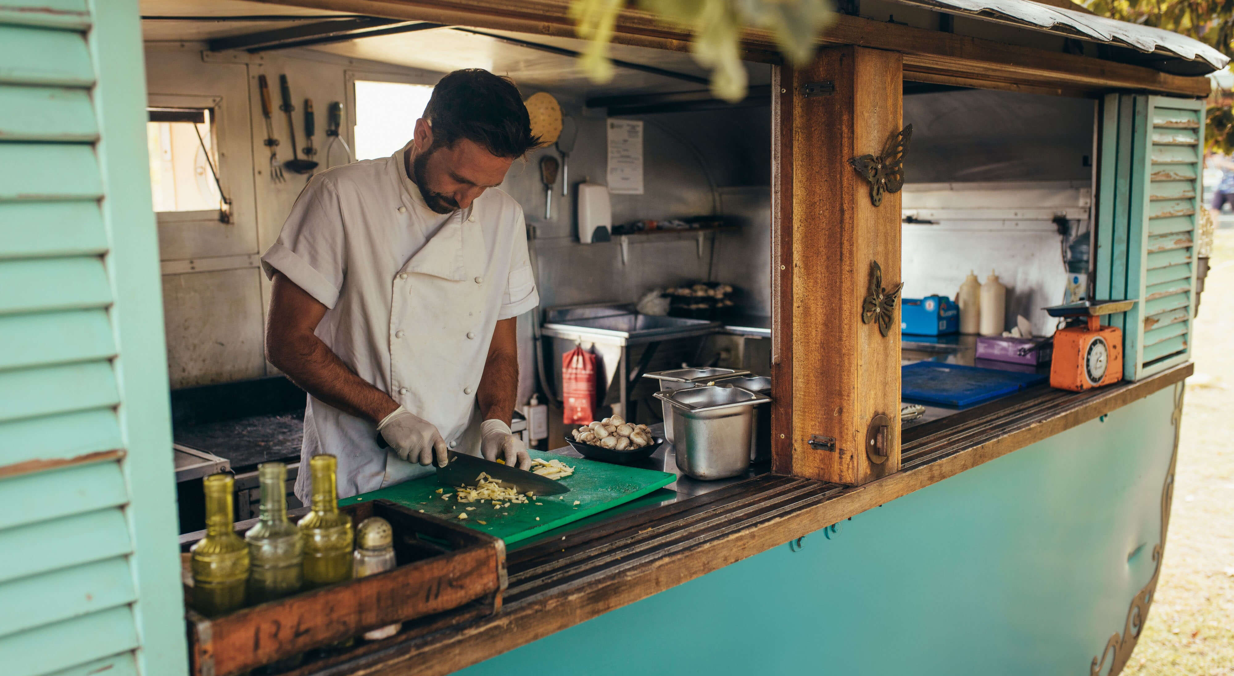 food truck owner chopping ingredients inside a turquoise rustic-themed food truck