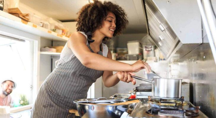 woman preparing food in a food truck kitchen