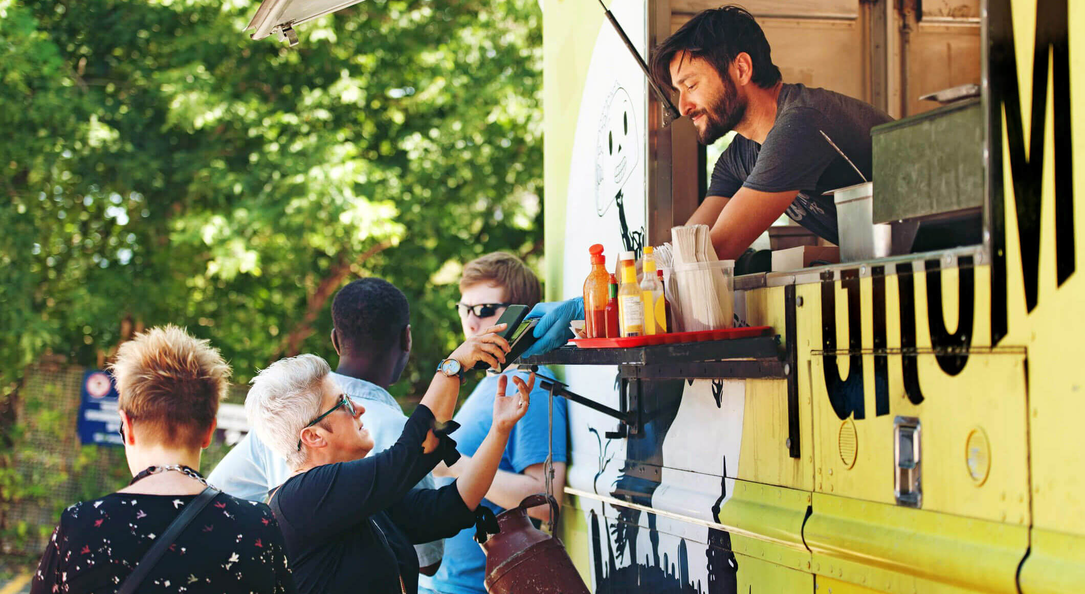 customer being served by a man inside a yellow-colored food truck