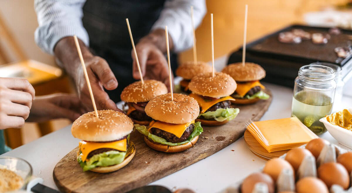 six hamburgers in a stick served on a wooden plate