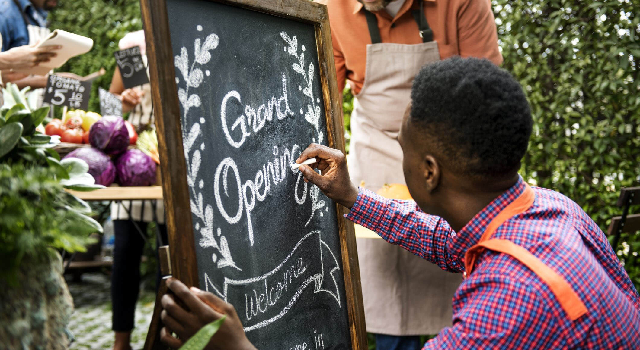 food truck owner designing a grand opening sign on a chalkboard