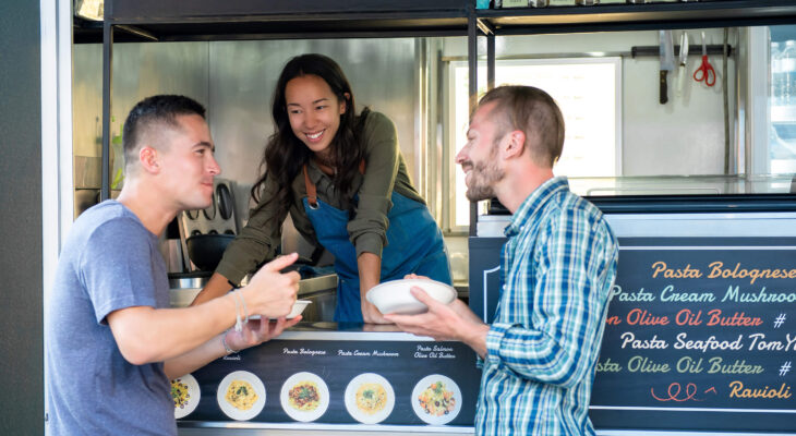 three people in a food truck talking to each other