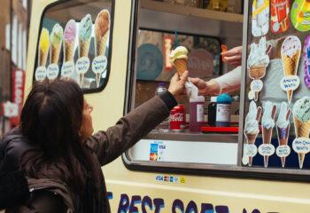 ice cream truck owner handing ice cream to a customer