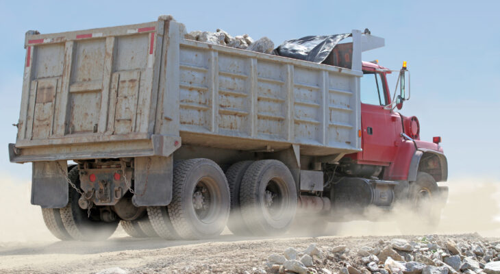 red dump truck transporting boulders on a dusty construction site