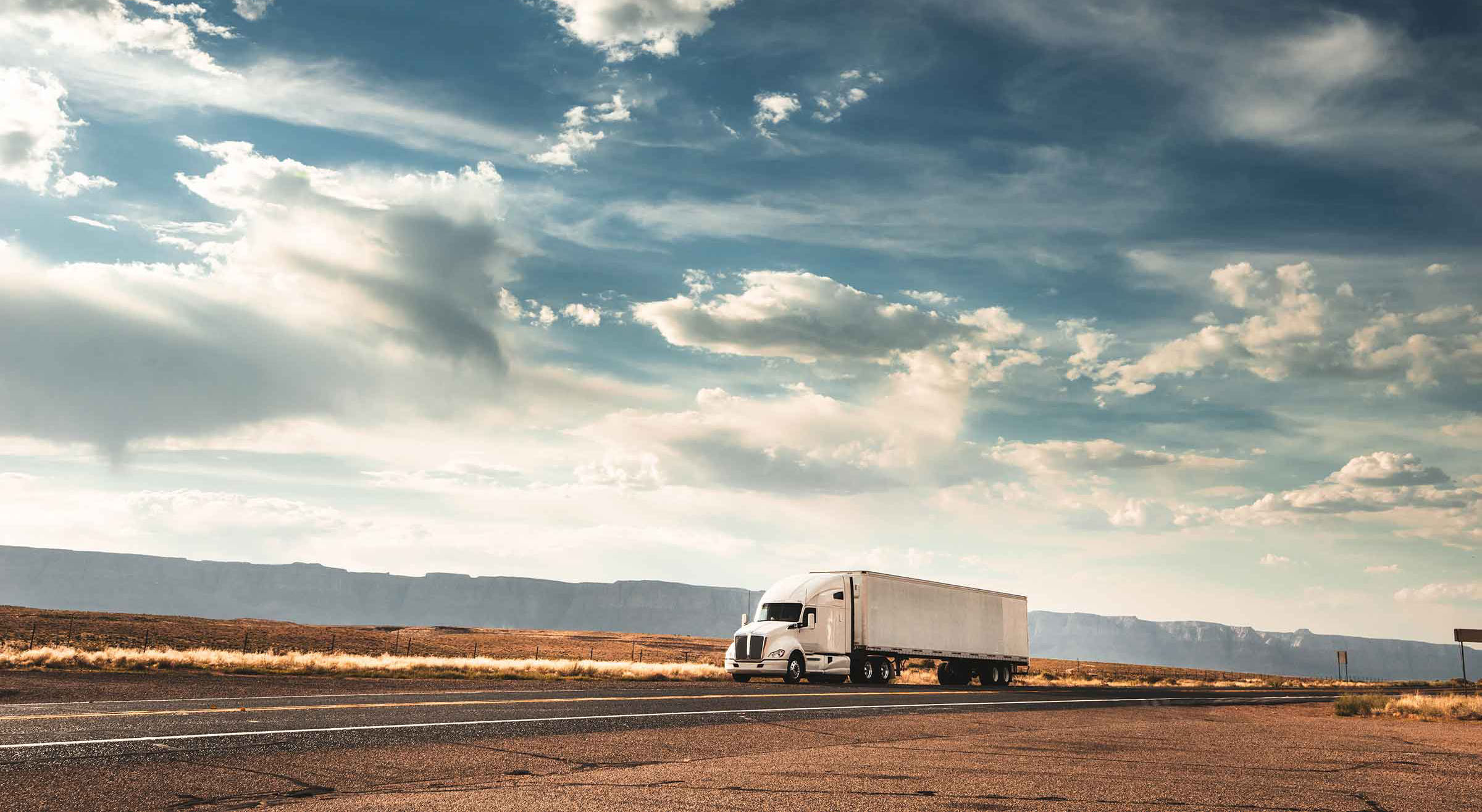 lone white long-haul truck on a deserted road