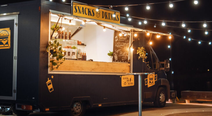 dark gray food truck selling snacks and drinks in the evening