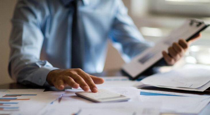 businessman calculating taxes on a calculator