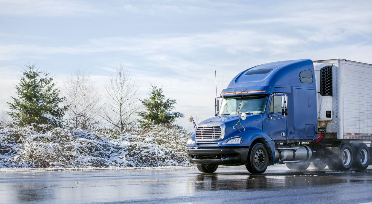 blue semi-truck being driven on a slippery road during winter