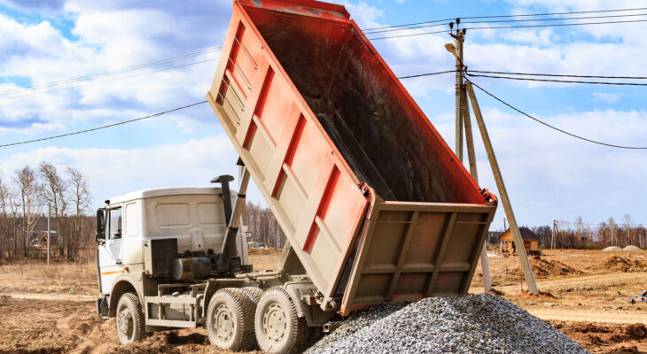 construction gravel unloaded by an orange dump truck on a vacant lot