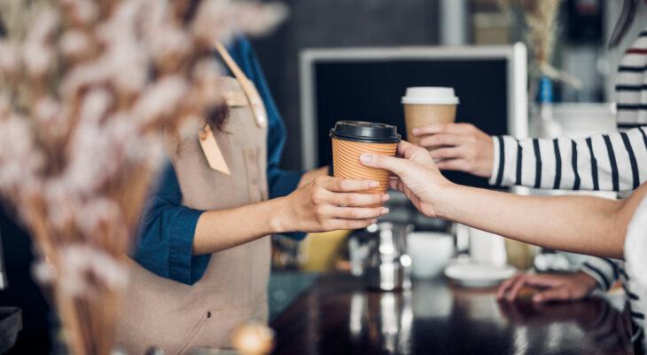 barista handing coffee to customers