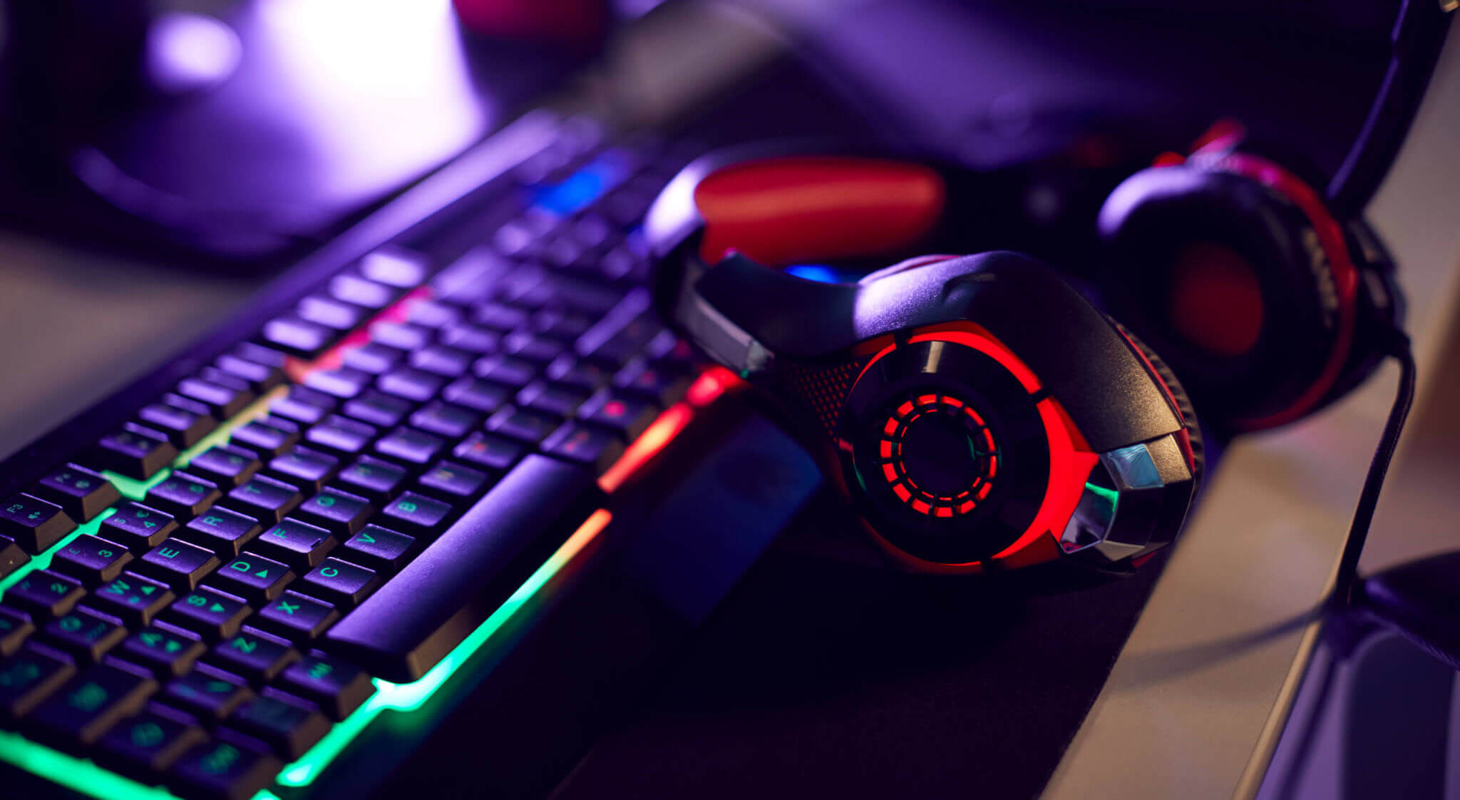 RGB gaming keyboard and headset on a desktop