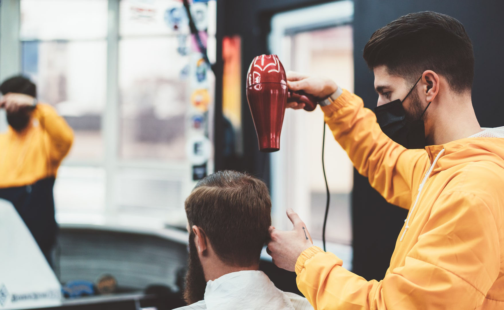 barber wearing a face mask during a pandemic while blow drying customer's hair