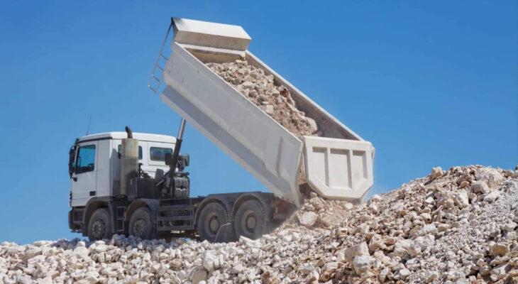 white dump truck unloading crushed rocks