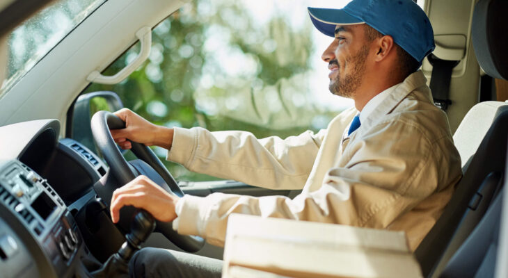 smiling delivery truck driver while holding gear stick