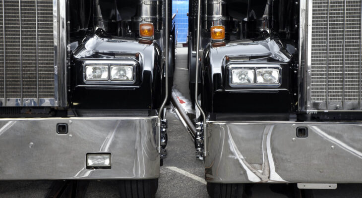 two black semi-trucks parked next to each other