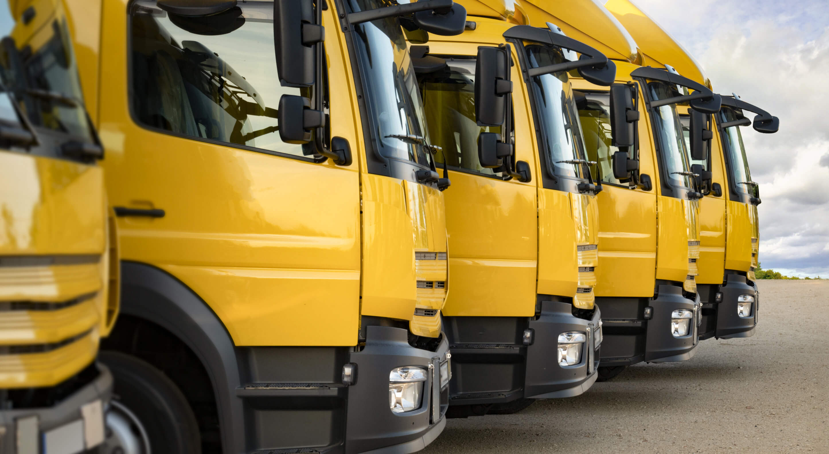 yellow day cab trucks parked in a row