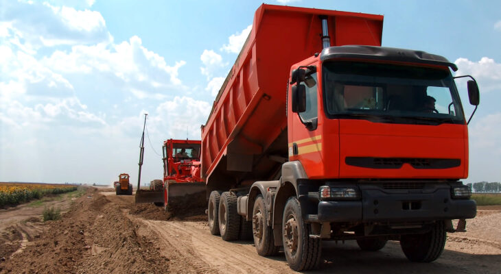 red dump truck on a vacant lot