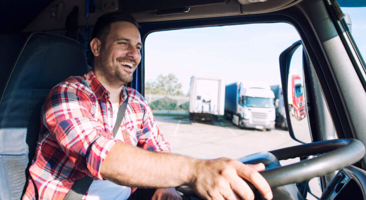 happy smiling truck driver in a semi truck