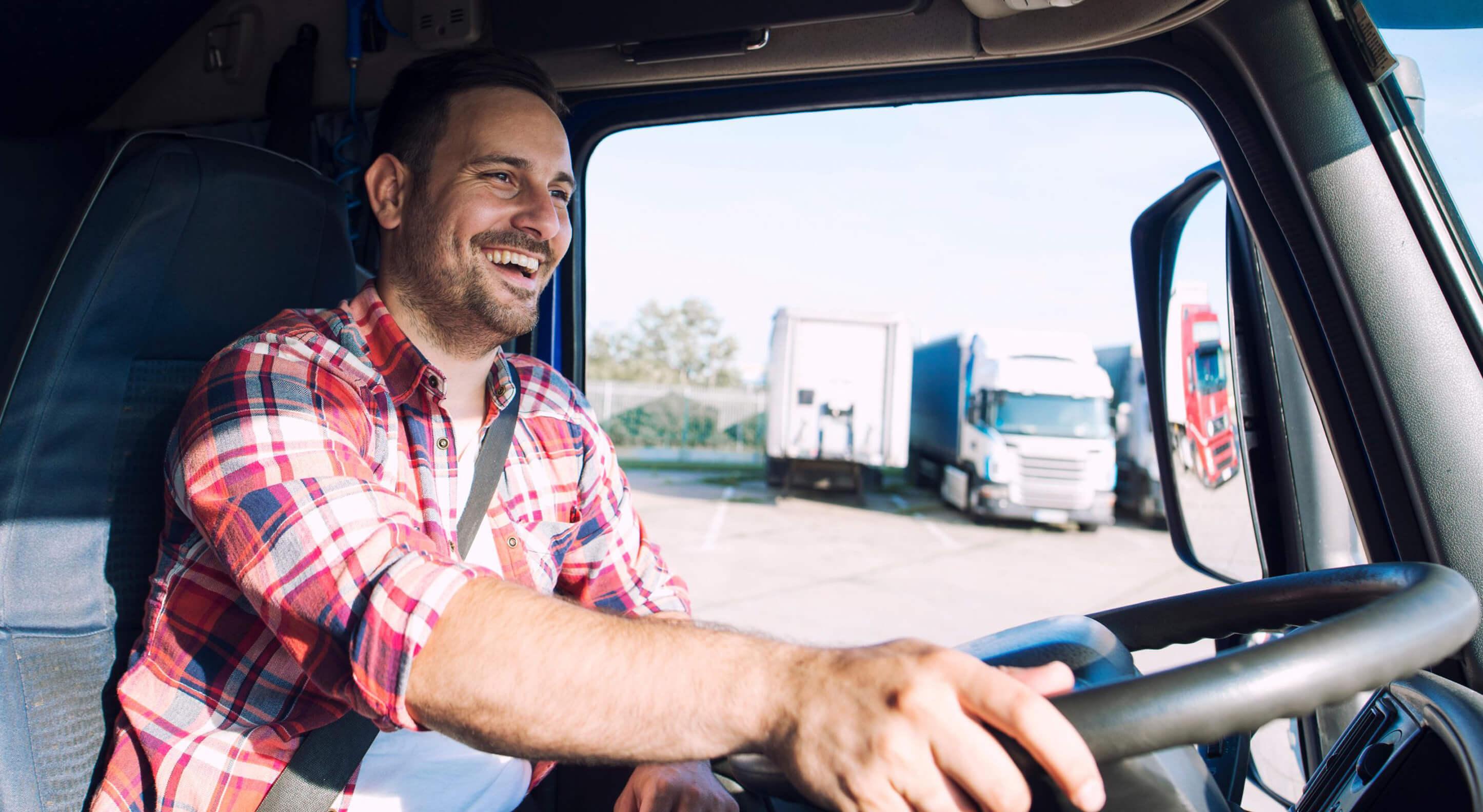 happy smiling truck driver in a semi truck