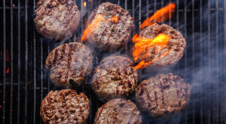 burger being cooked on a barbecue grill