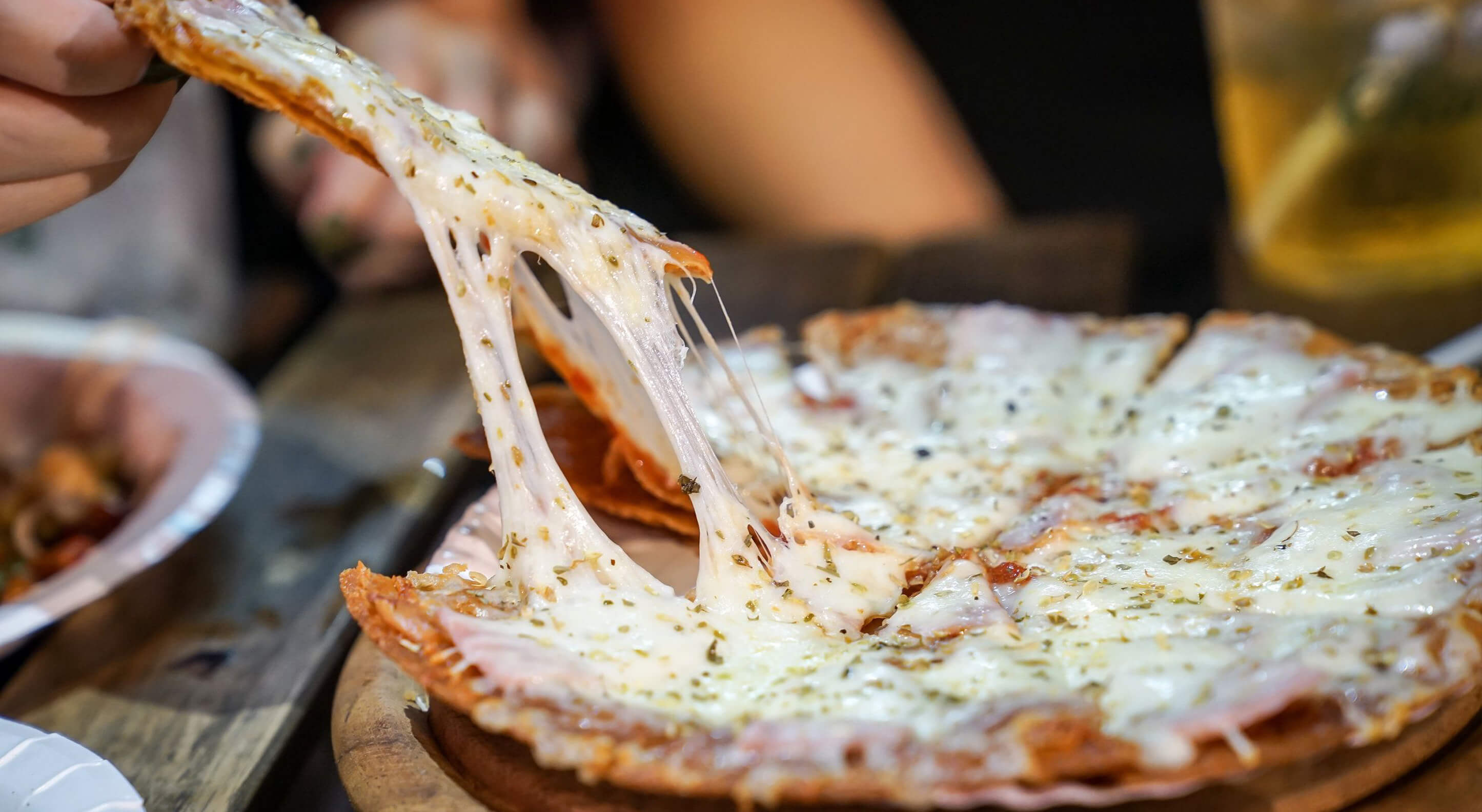 person's hand taking a slice of pizza from a pizza plate