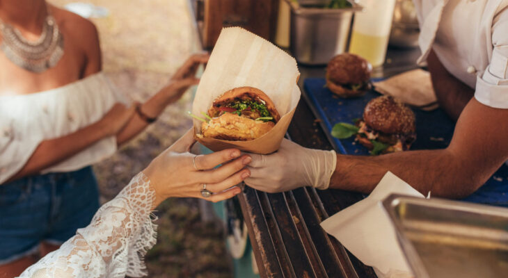 woman's hand receiving a burger from a catering food truck owner