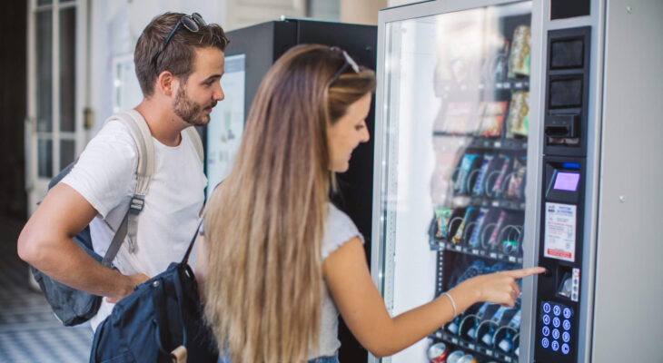 two university students taking buying snacks from a vending machine