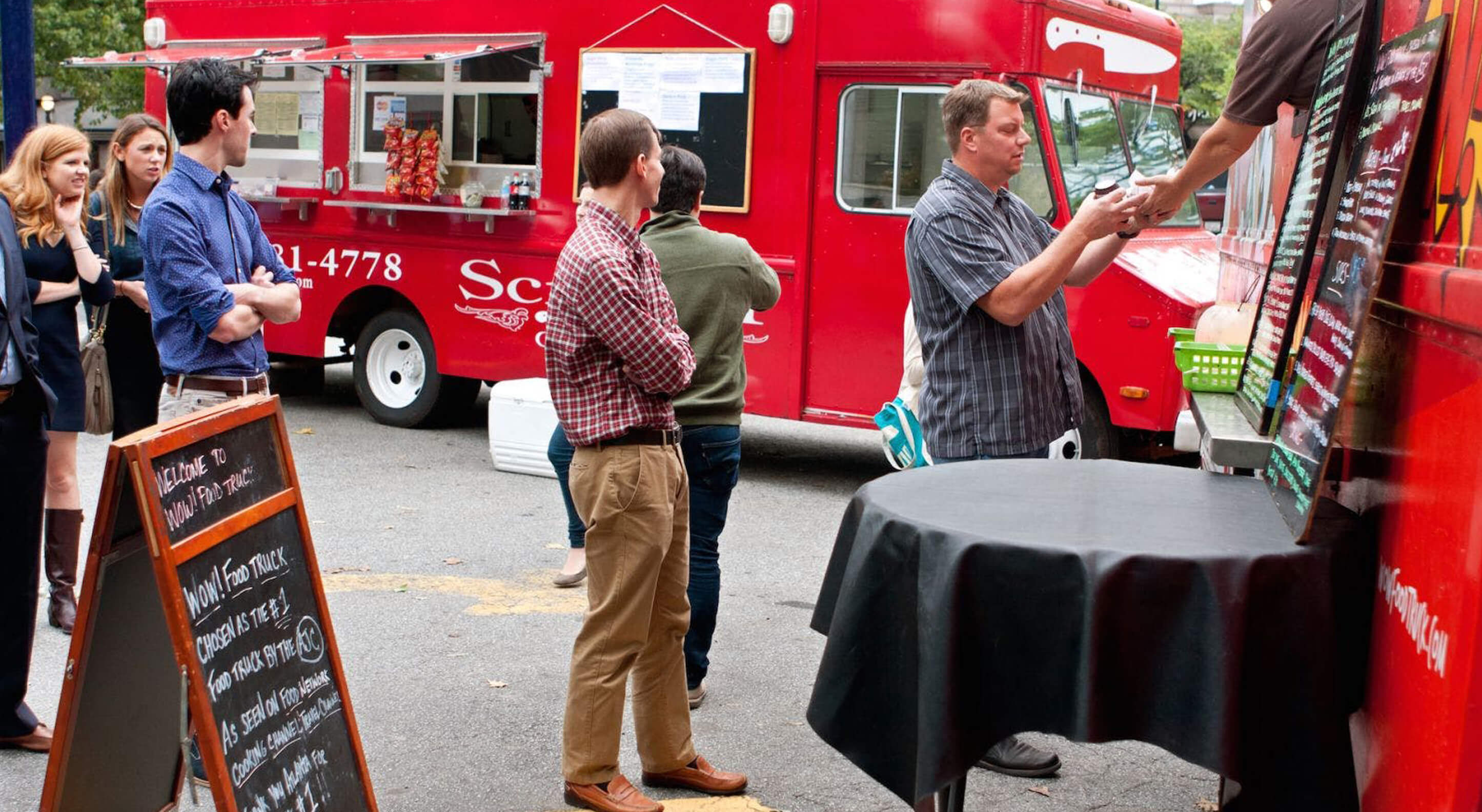 group of people lined up in front of a food truck