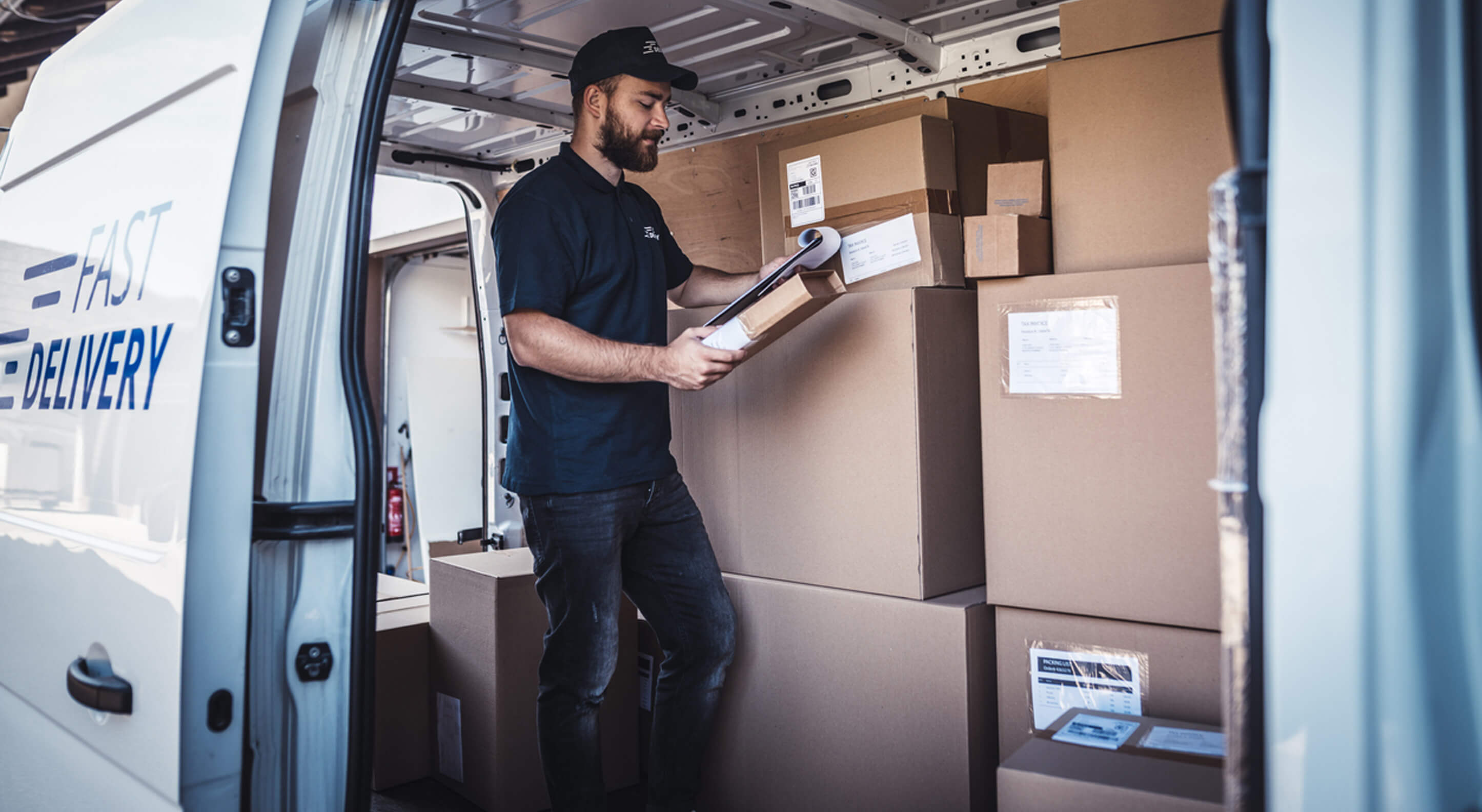 a young delivery man checking a list of packages inside a step van