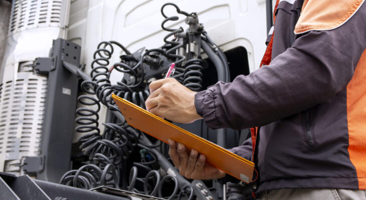 truck driver holding a clipboard while inspecting the engine of a day cab truck for daily safetycheck
