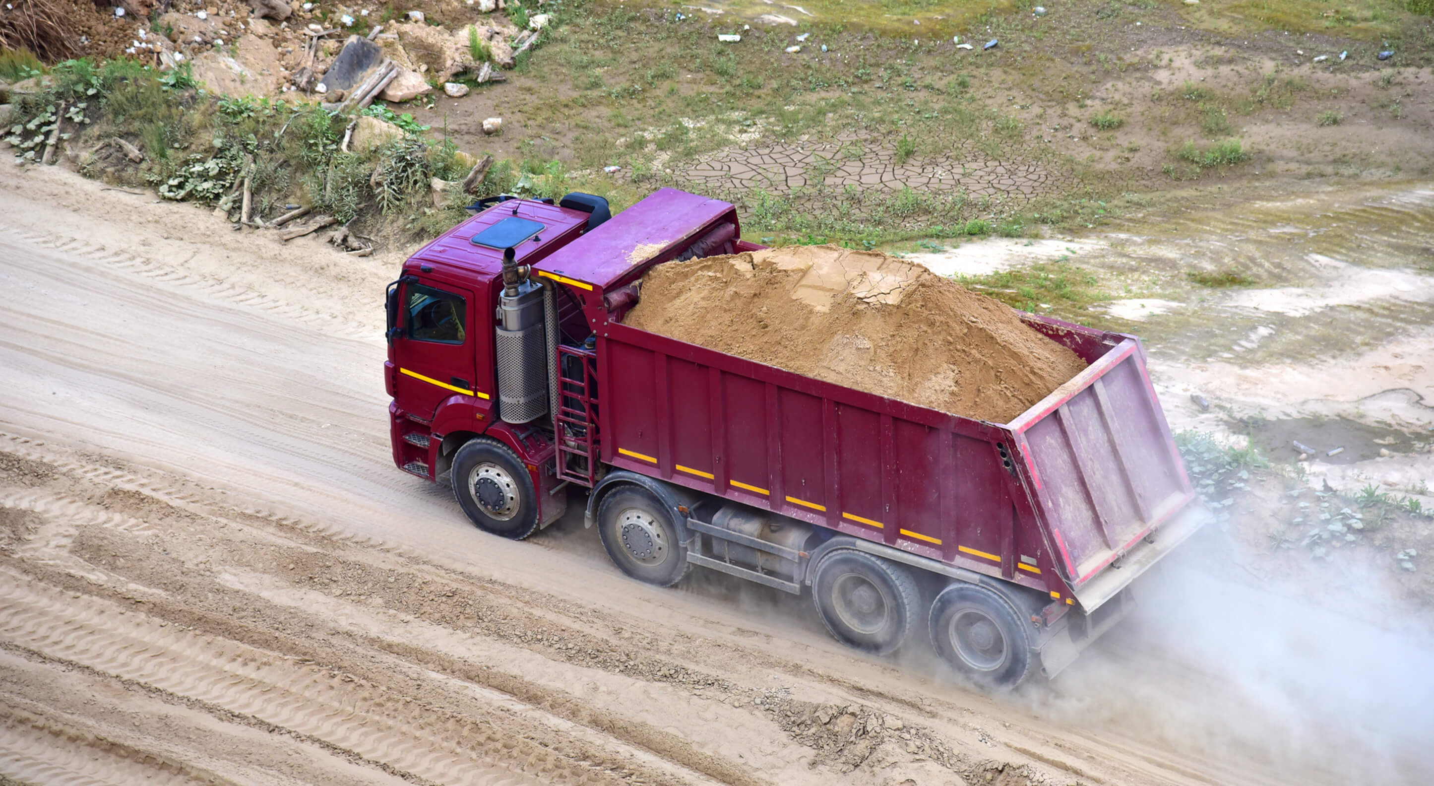dump truck transports sand in an open pit mine