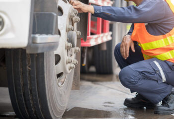 truck inspector checking a semi truck before transporting goods