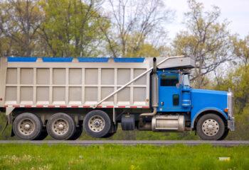 blue tarped dump truck in a grassy road