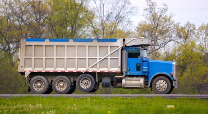 blue tarped dump truck in a grassy road