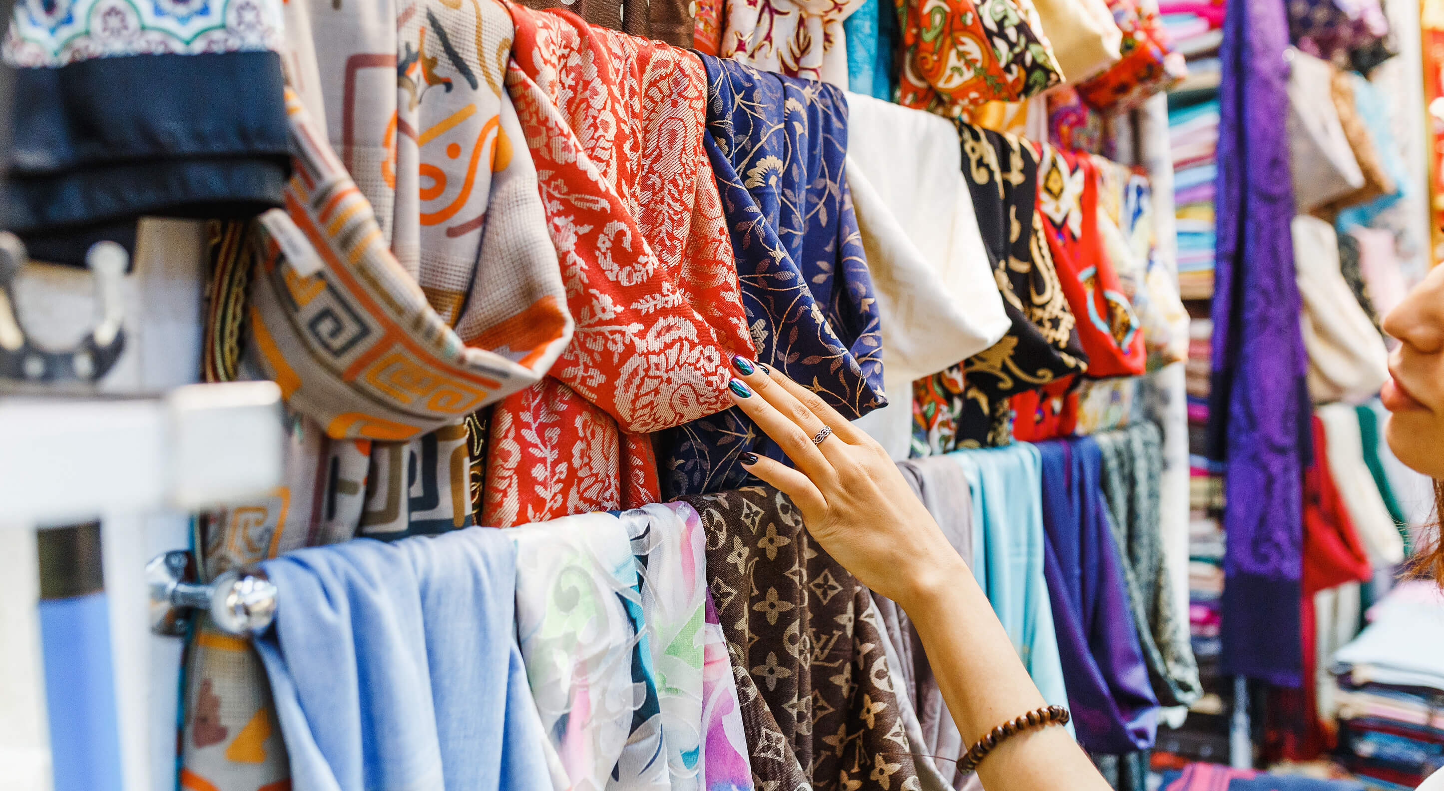 young woman shopping for a new colorful scarf at a mobile boutique