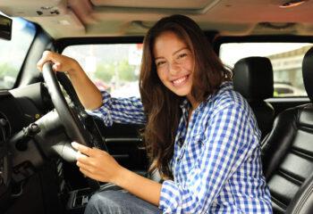 female truck driver smiling inside a semi truck