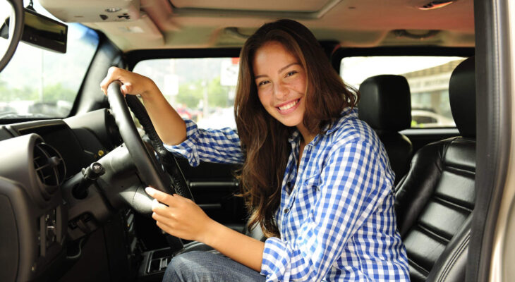 female truck driver smiling inside a semi truck