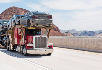 red semi-truck transporting a number of cars on a highway