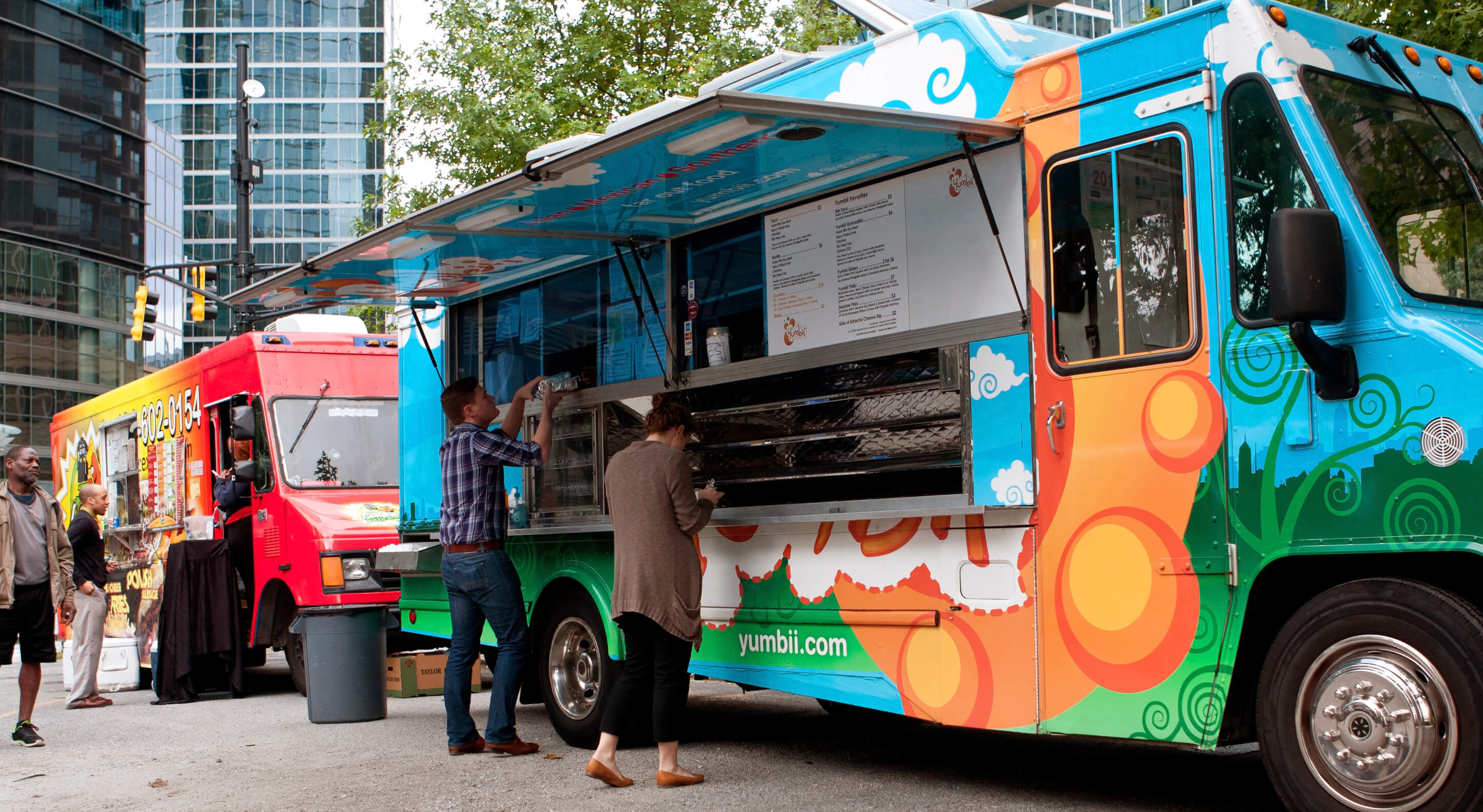 two colorful food trucks in a city center