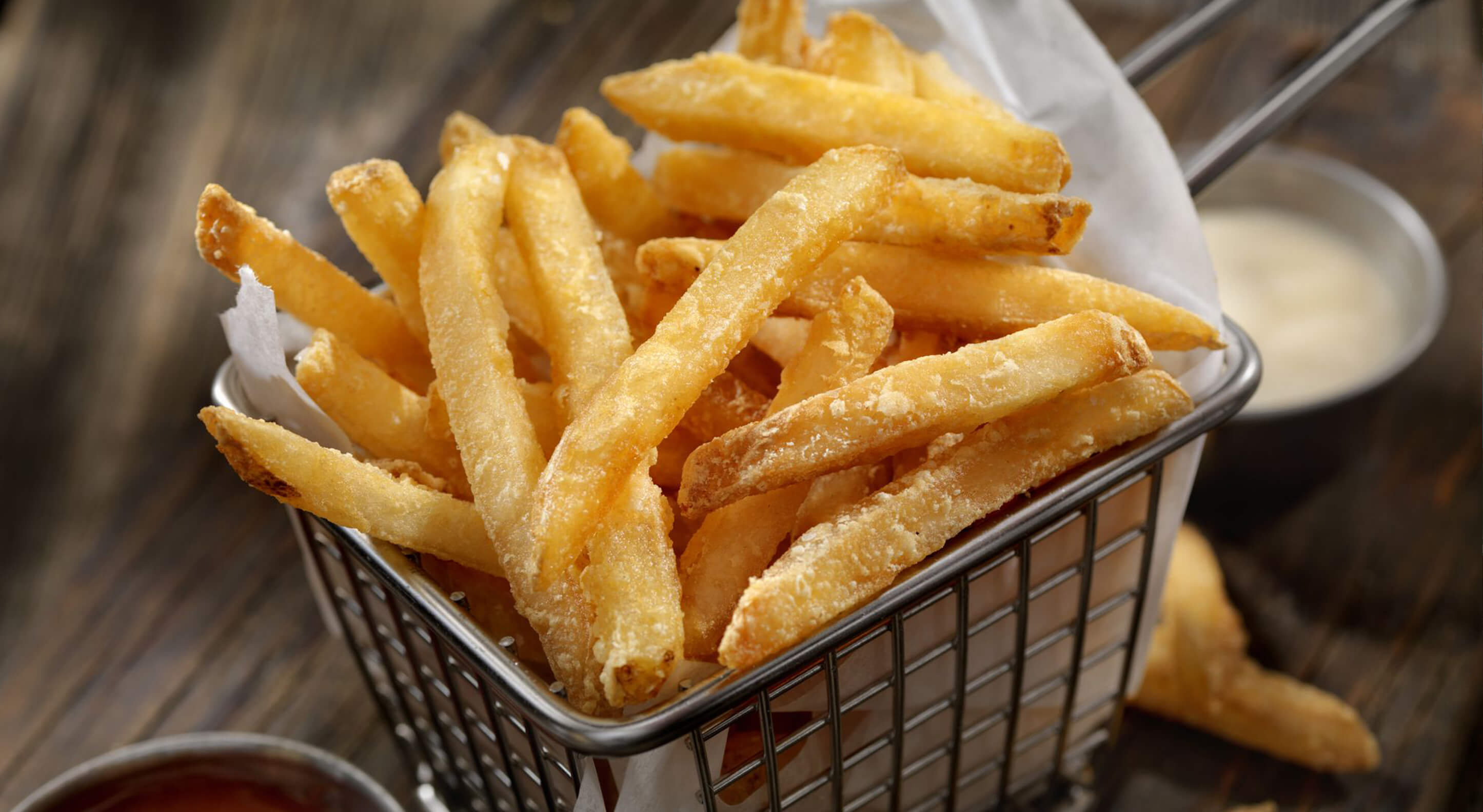 bucket of freshly cooked french fries with ranch dip on the side
