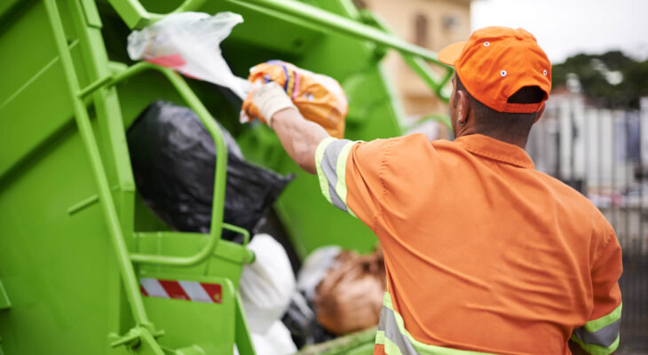 garbage collection worker in front of a green garbage dump truck collecting garbage