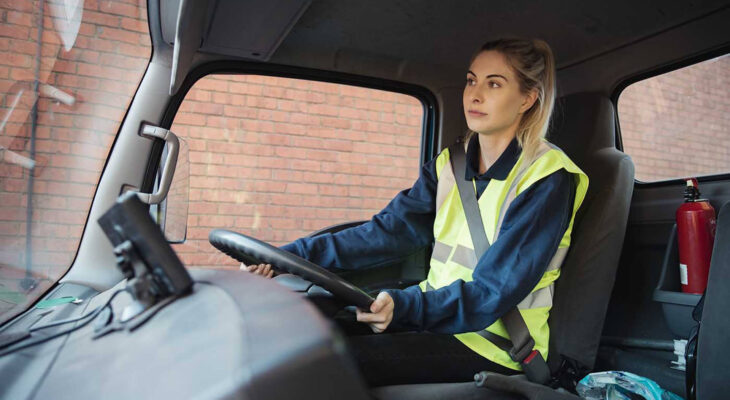 young female worker in a semi truck driving to work