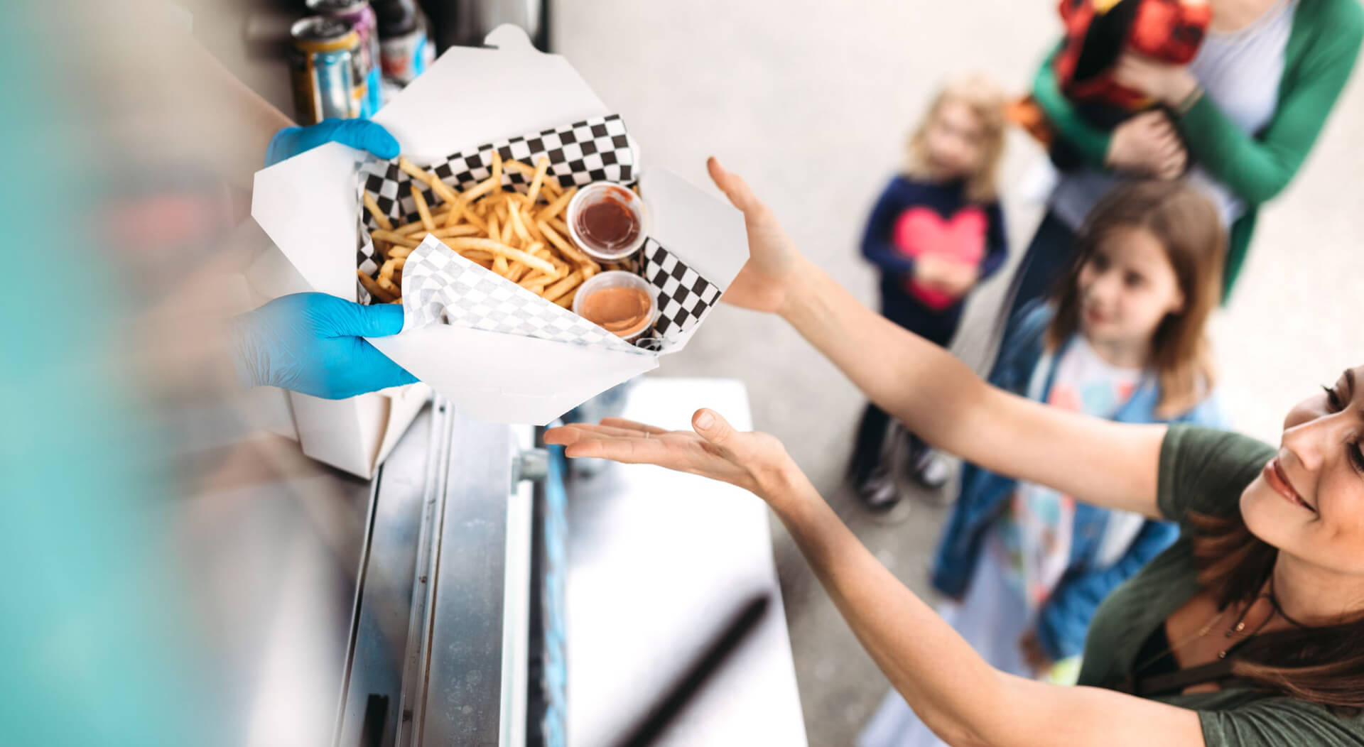 woman smiling as she receives her order of gourmet french fries with special dipping sauce at a food truck